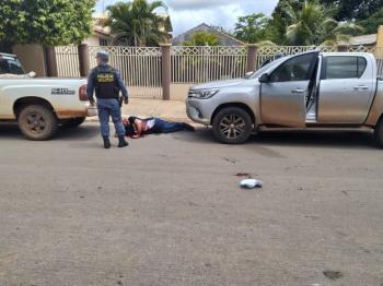 Polícia Militar se depara com um dos alvos da execução, alvejado e ensaguentado, deitado no asfalto, onde é possível ver marcas de sangue das vítimas