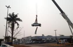 Para conscientizar a população sobre o trânsito, carro batido é suspenso por guindaste e exposto em avenida de Tangará da Serra