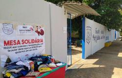 Mesa solidária com alimentos e doações é montada do lado de fora de escola em MT